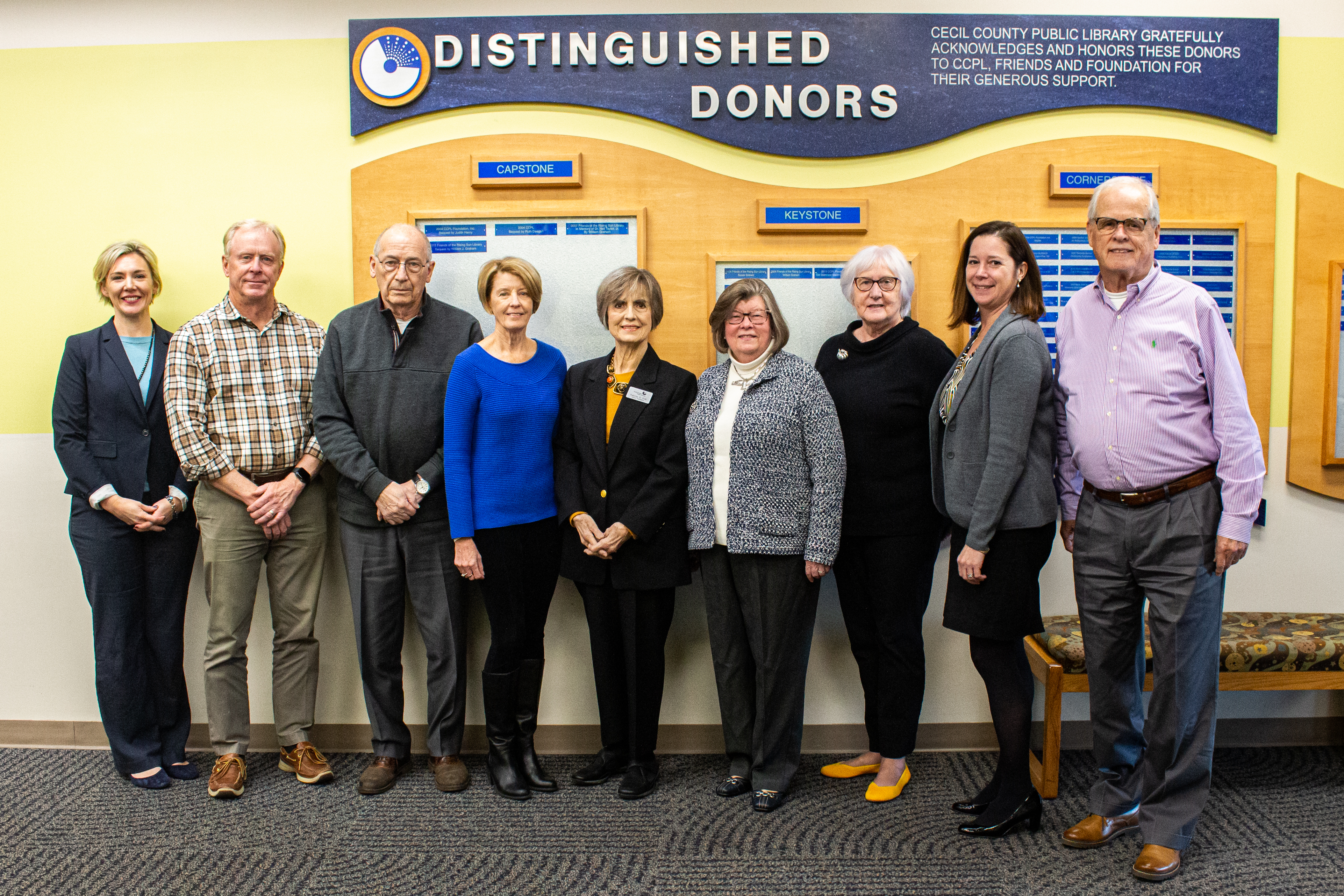 Friends Foundation members posing in front of the Distinguished Donors wall